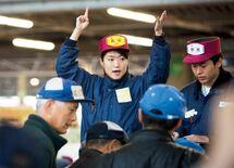 早朝の競り台で相場を仕切る女性販売人
